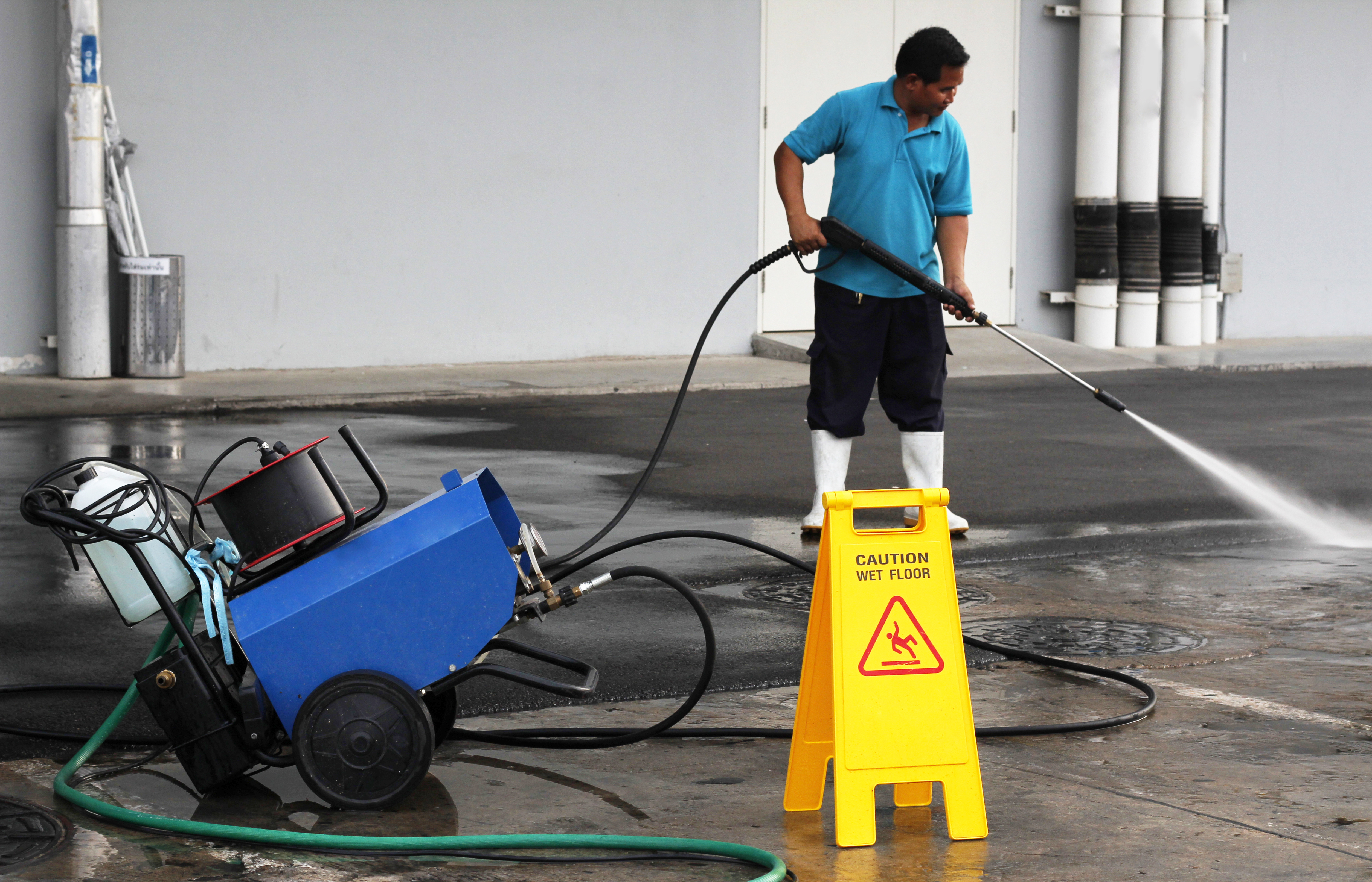 worker-cleaning-floor-with-air-high-pres