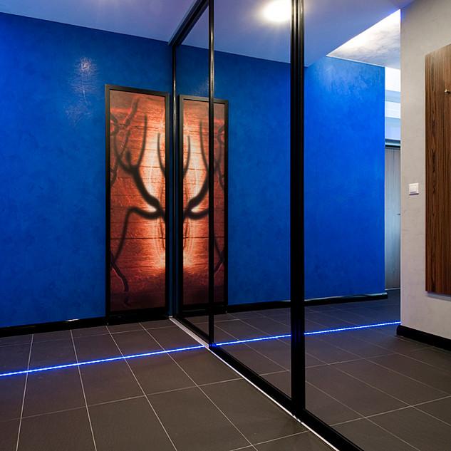 zrkadlo na posuvných dverách šatníka, okrem optického zväčšenia vstupného priestoru, je aktívnym doplnkom výtvarnej fotografie a LED pásu v podlahe, ktoré znásobuje