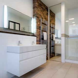 za zrkadlom v kúpeľni, ktoré je v ráme a na pántoch, je priestor pre práčku a sušičku