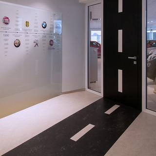 detail napojenia grafického riešenia podlahy a dverí ako cesty v kancelárii autosalónu