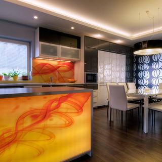 nasvietená abstraktná fotografia obkladu nad pracovnou plochou a podsvietený pult kuchyne sú farebnými dominantami inak čierno-bieleho priestoru kuchyne a jedálne rodinného domu