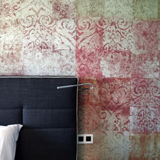 detail presnej polohy čela postele voči vzoru dekoračnej tapety a vypínačom svietidiel