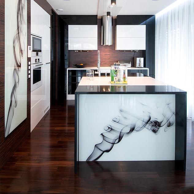 abstraktné fotografie pod sklom barového pultu a bočnej steny kozuba dopĺňajú štýl riešenia kuchyne rodinného domu