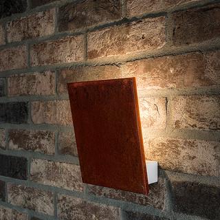 detail jednoduchého nástenného svietidla Exenia, ktoré nepriamym osvetlením zvýrazňuje štruktúru tehlového obkladu