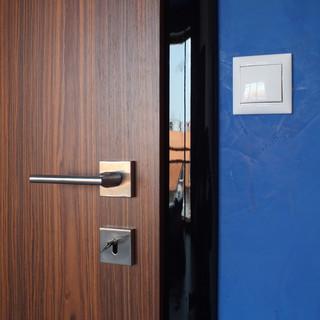 detail kombinácie mareriálov: matnú dýhu dverí a matný povrch steny Stucco delí vysoko lesklá čierna zárubeň