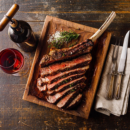 Grilled sliced Tomahawk Steak on bone and glass of Red wine on wooden background_edited.jp
