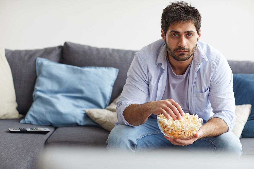Young unshaven man eating popcorn