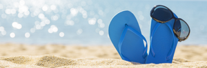 Flipflops on beach with sunglasses