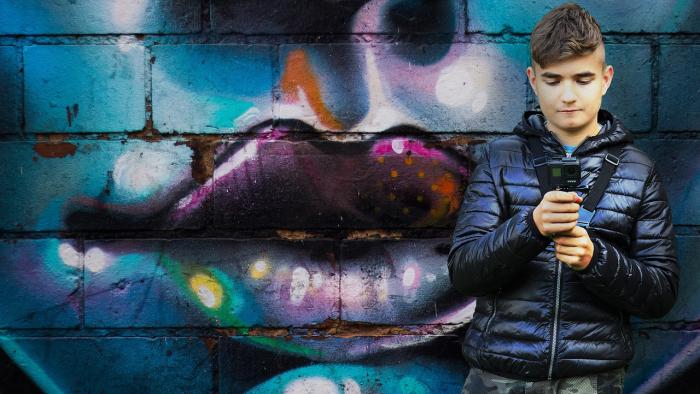 נער על רקע קיר עם גרפיטי, אוחז במצלמת וידאו