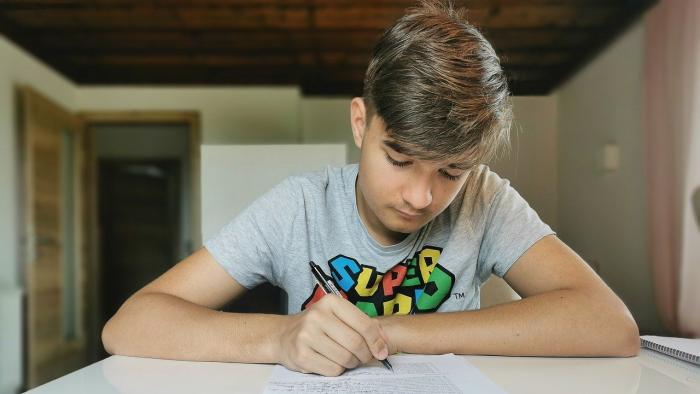 נער יושב וכותב