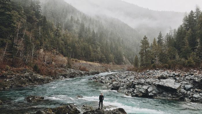 בחור עומד מול נהר גועש
