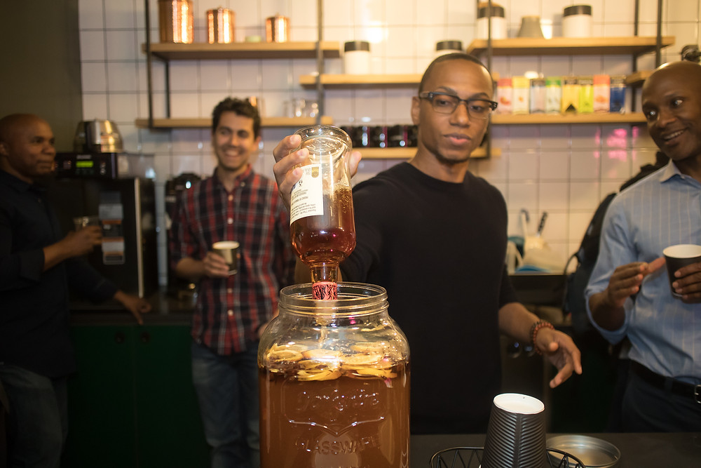 Handsome Man Pouring Angostura Rum into Spiced Tea