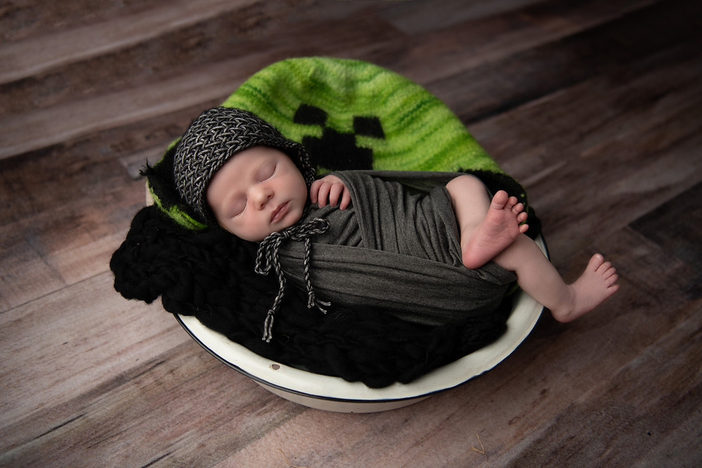 baby boy sleeping in bowl with minecraft hat