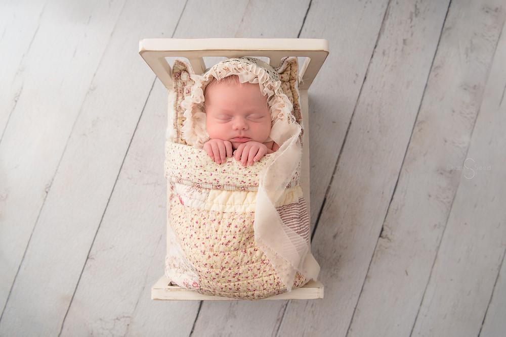 newborn baby in bed prop