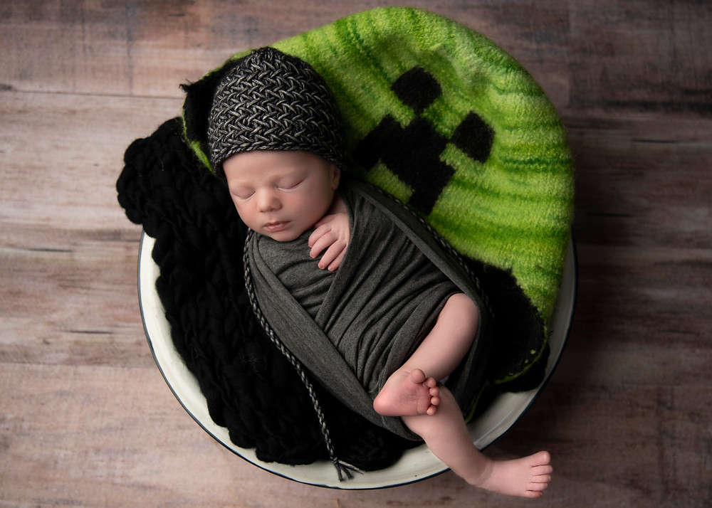 Newborn baby boy in bowl with Minecraft hat