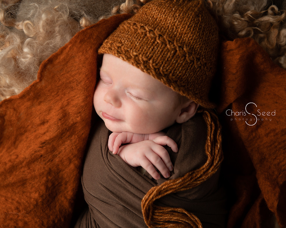 smiling newborn boy with orange bonnet