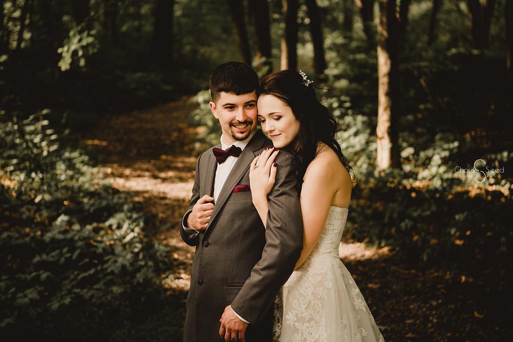 bride holds groom behind on shoulders