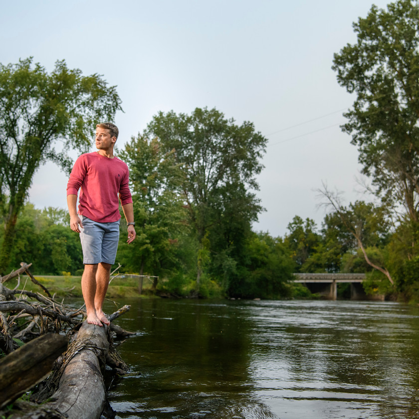 standing on log in river