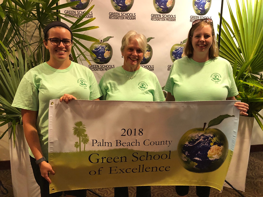 Miss A, Ms. Pat, and Mrs. Hanson hold up the new banner recognizing BFA as a Green School of Excellence for 2018