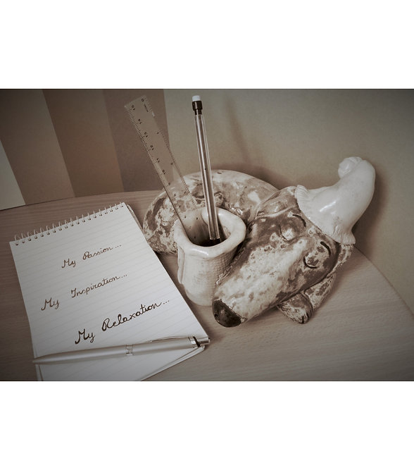 Photograph of a ceramic sleeping dog with a pot for flowers or stationary and a notebook with pen which says my passion, my inspiration, my relaxation