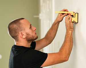Jesse handyman measuring before hanging shelves