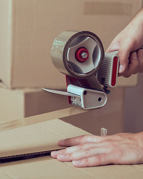 Hands holding packing tape dispenser sealing up cardboard moving box