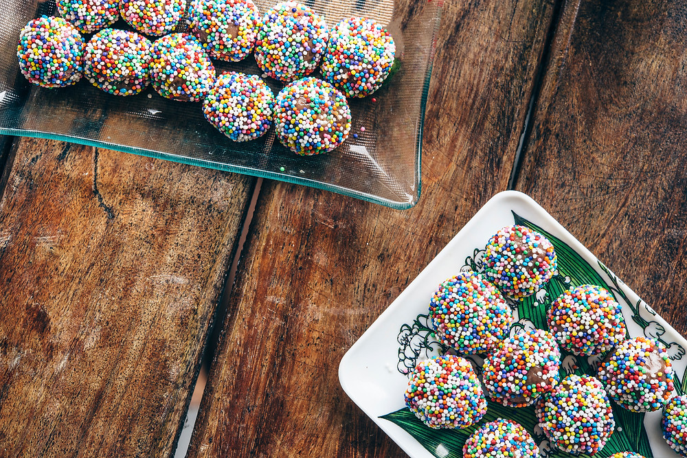 Two trays of colorful sprinkle chocolate balls on a wood table
