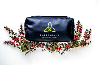 Three wings black travel pack nestled in flowers