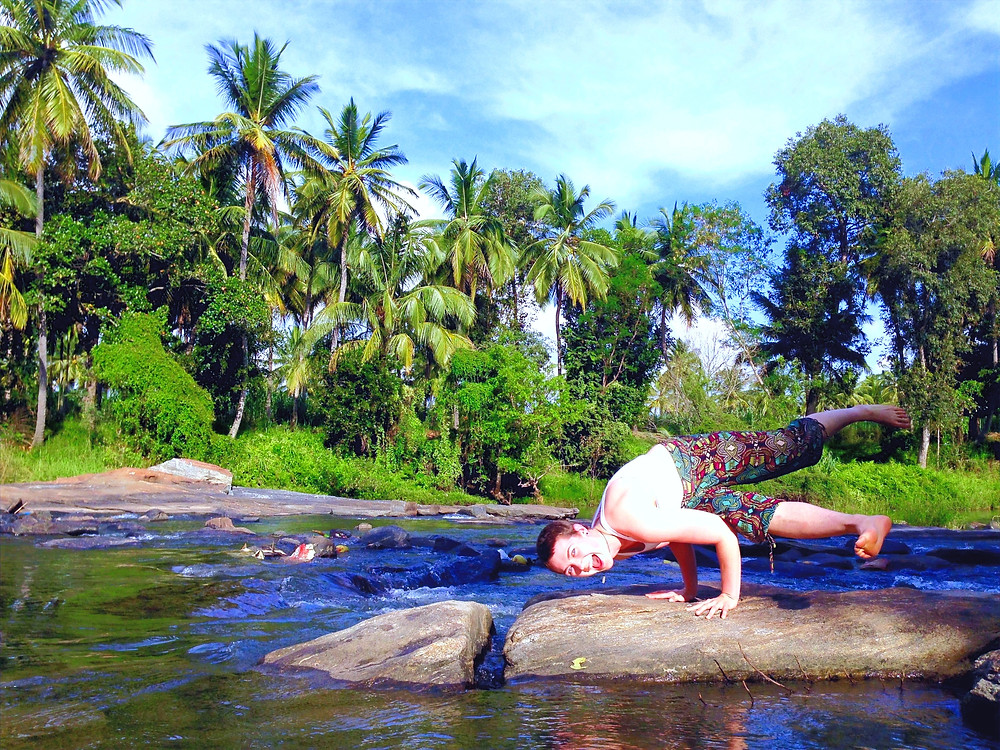 Kayla Luhrs playfully enjoys an arm balance on the banks of a river in Mysore, India.