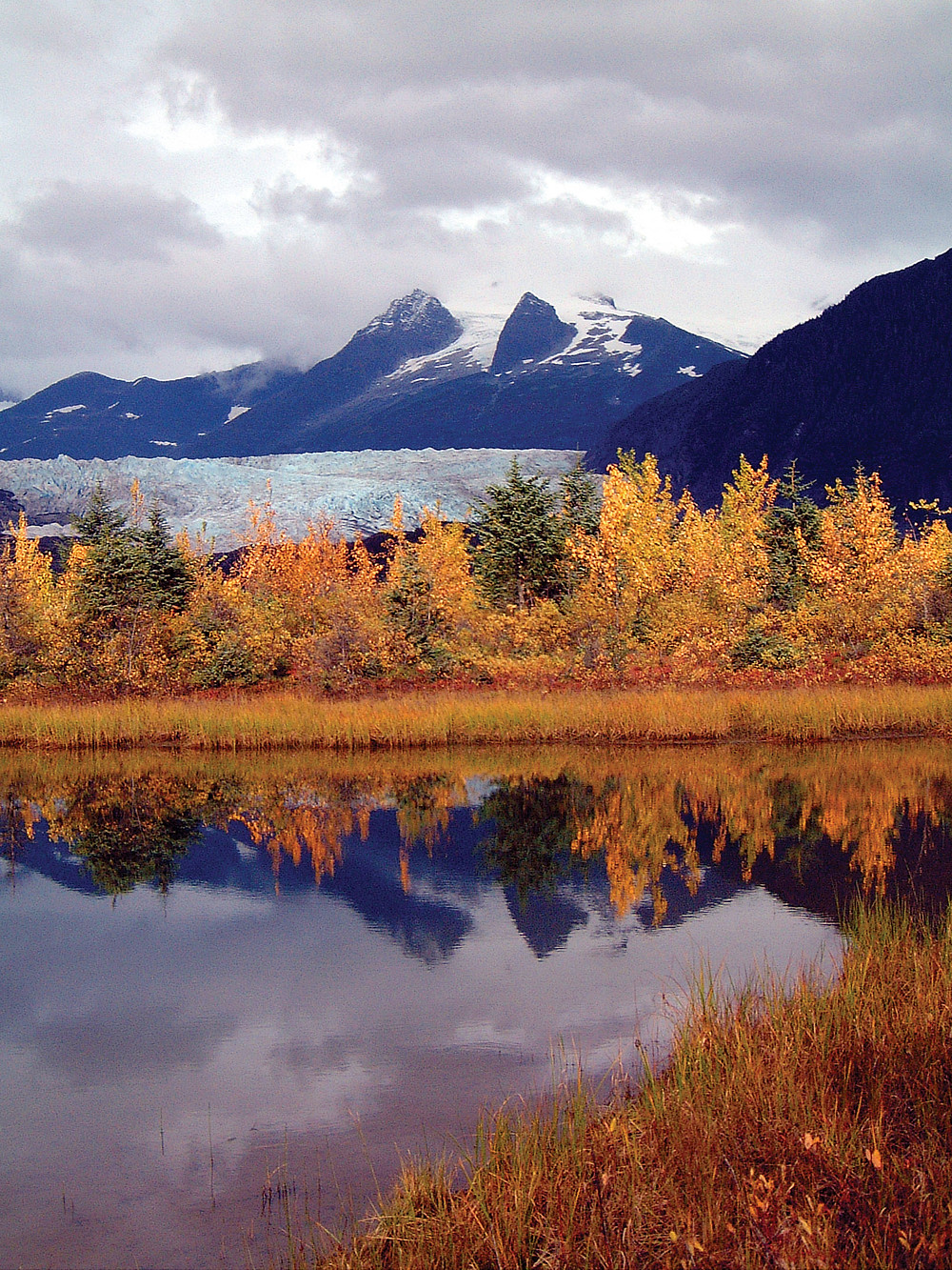 Crystal clear water reflects fall foliage and glacier in Juneau, Alaska.