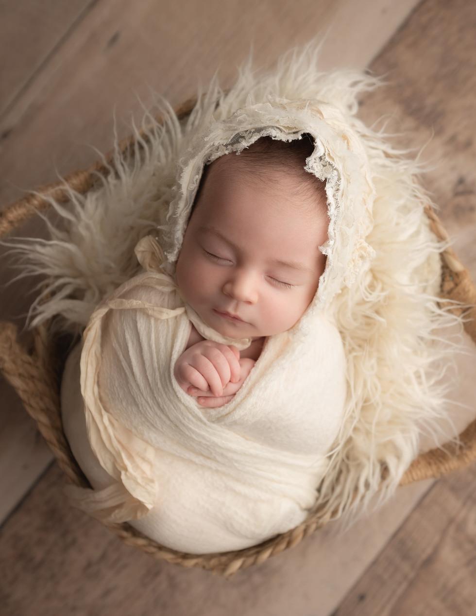 Newborn baby in basket with cream bonnet