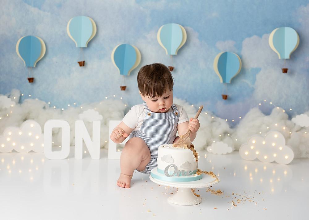 Baby eating cake in cake smash photo shoot