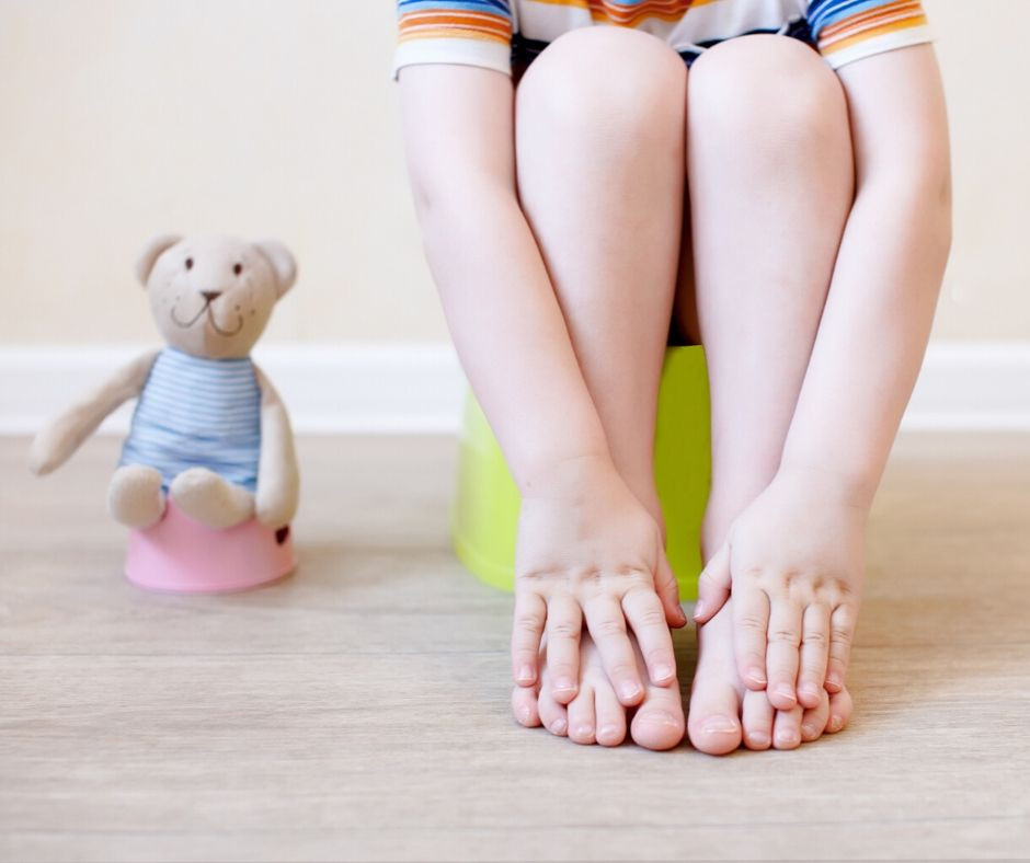 child with toy on potty training