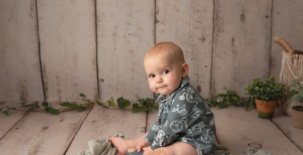 7 month old baby boy in grey posing on a wooden backdrop for sitting photo session