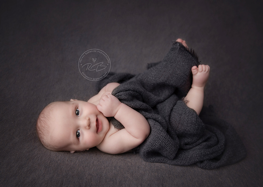 4 month old baby boy on grey backdrop during photo shoot in Salisbury, Wiltshire