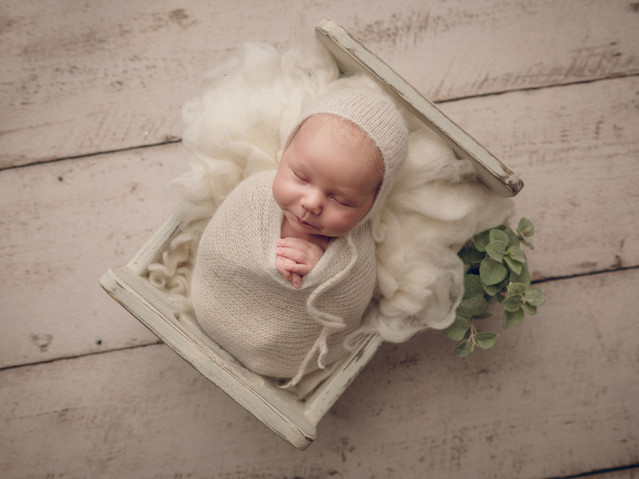 Baby in bed with bonnet