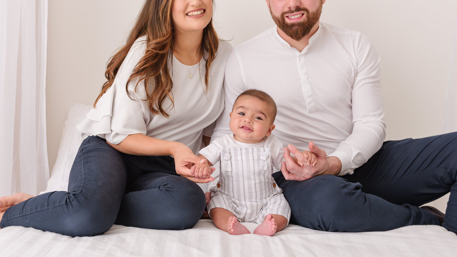 Family and baby posing on bed for baby photography session in wiltshire