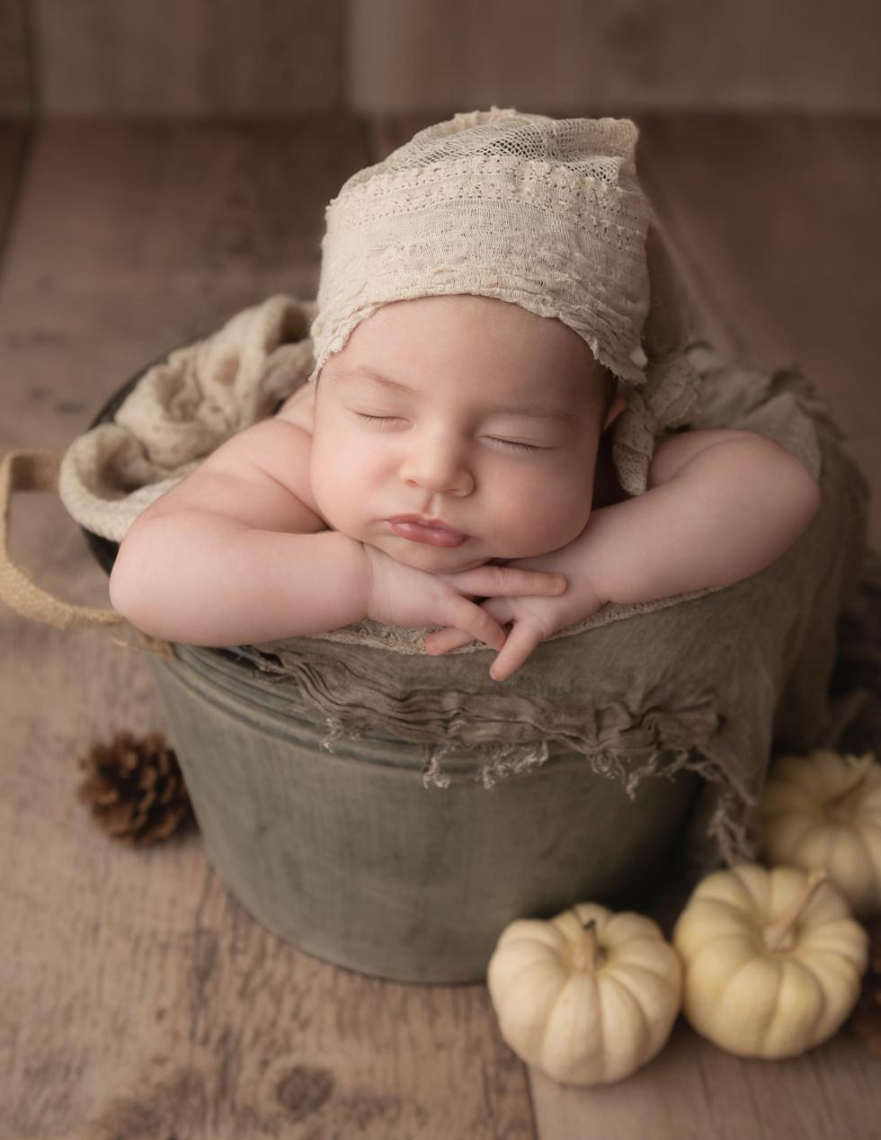 Newborn baby photography in bucket with pumpkins