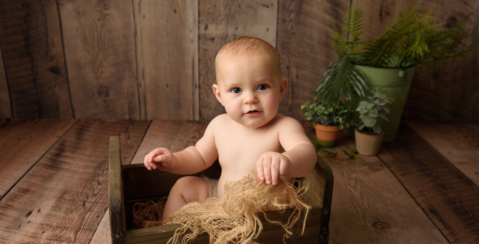7 month old baby posing in little bed for sitter photoshoot with Rachel Burnside Photography, Salisbury, Wiltshire