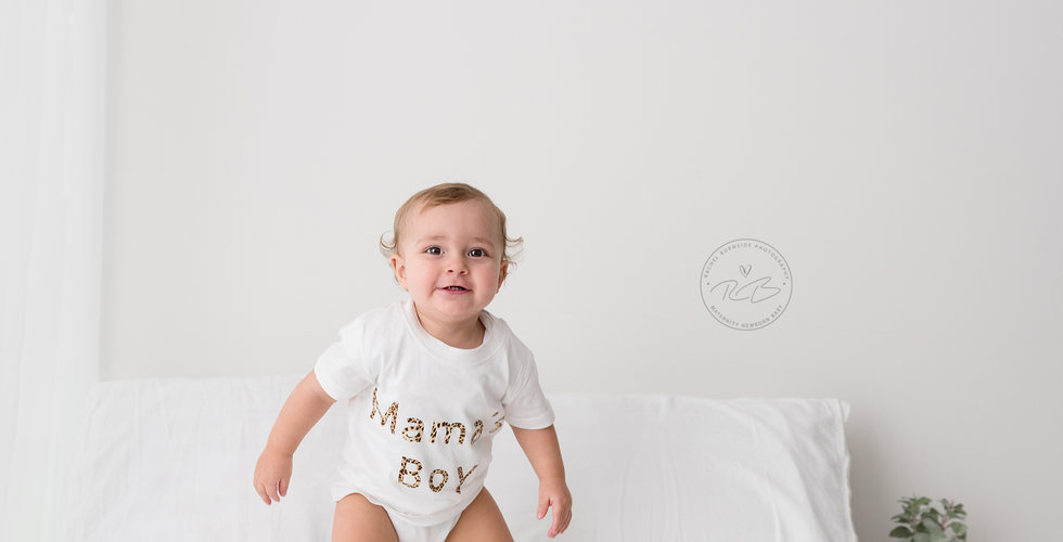 One Year old baby boy jumping on white bed during photo shoot in our Salisbury studio