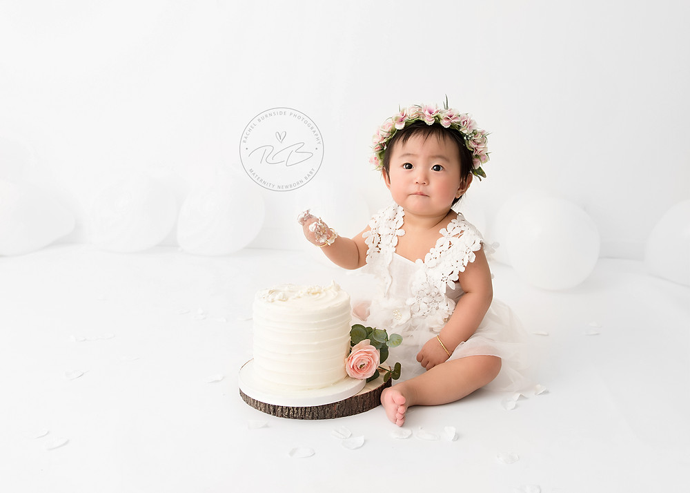 baby girl in pure white cake smash session with floral halo