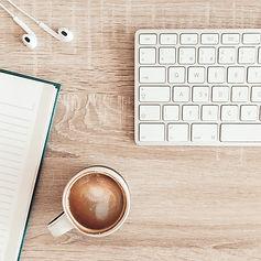 Kurse und Webinar ortsunabhängig. Notizbuch, Kaffee, Tastatur stehen auf dem Tisch zuhause.