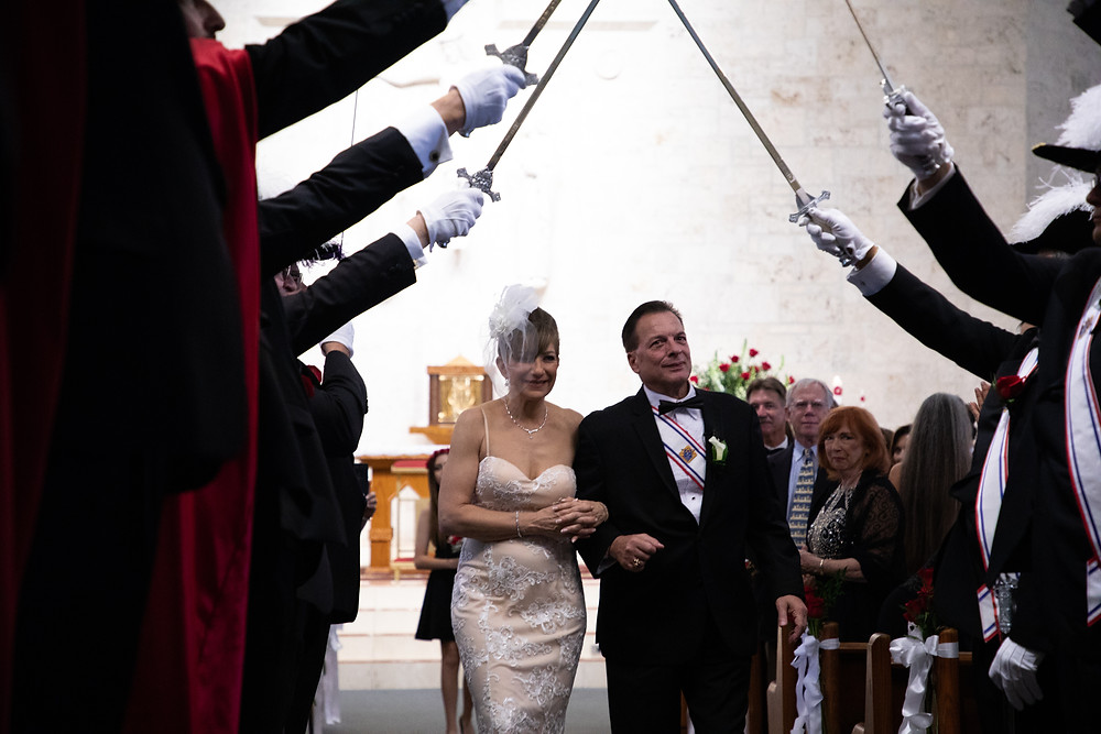 Miami wedding photographer captures image of husband and wife walking down the aisle under a brigade of knights.