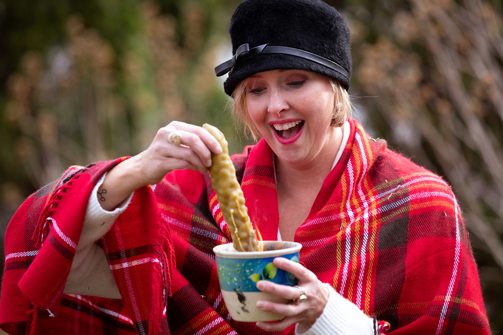 Cincinnati portrait photographer captures image of woman dipping food in coffee with winter clothes.