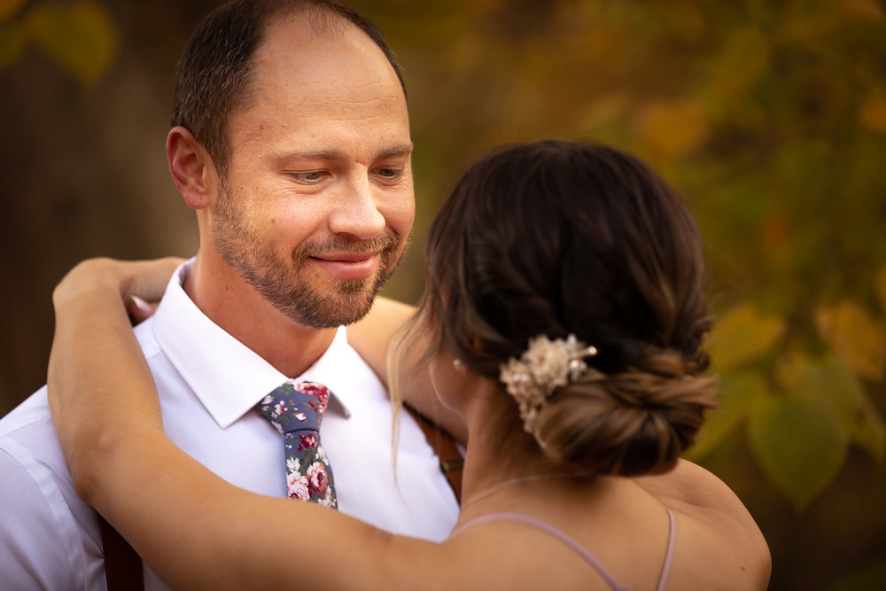 Cincinnati wedding photographer captures image of groom looking and bride's eyes smiling hugging each other.