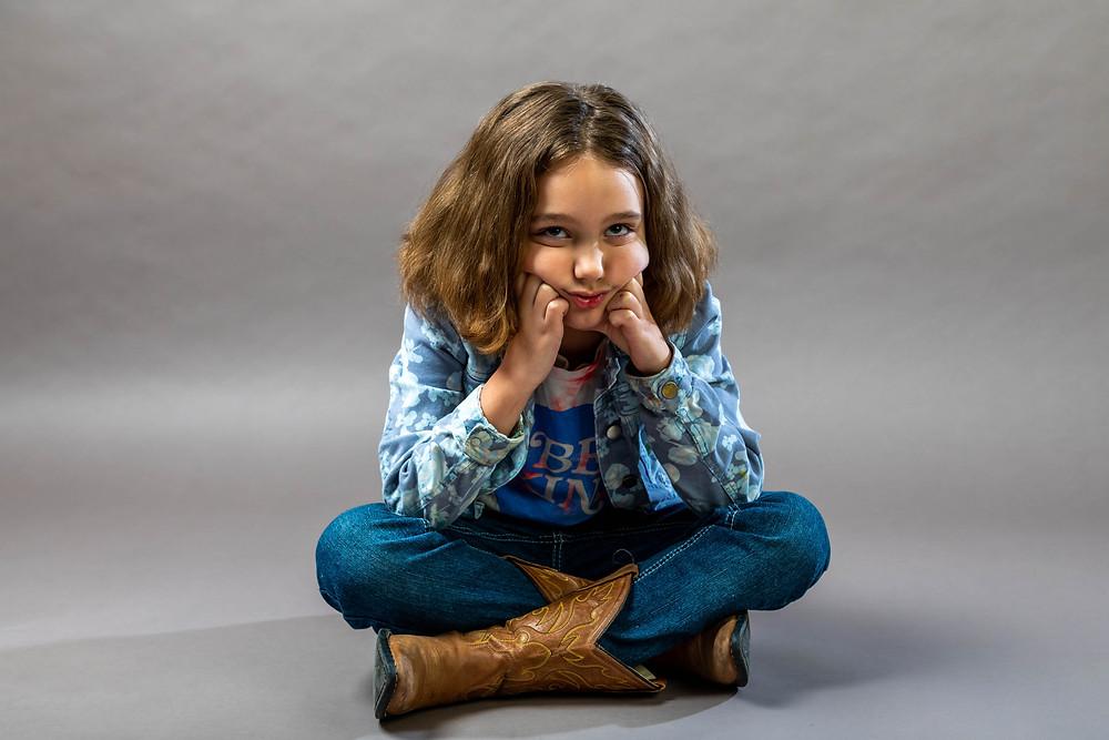 Cincinnati portrait photographer captures girl sitting on the floor looking up with her hands on her cheeks.