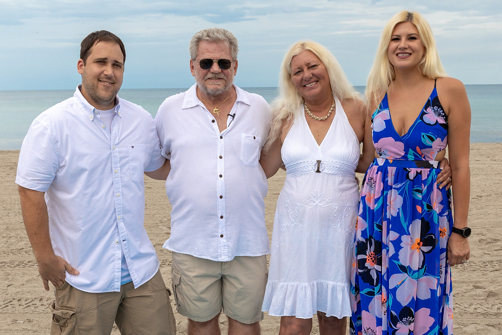Cincinnati wedding photographer captures image of elder husband and wife posing for a picture with their family in the beach.