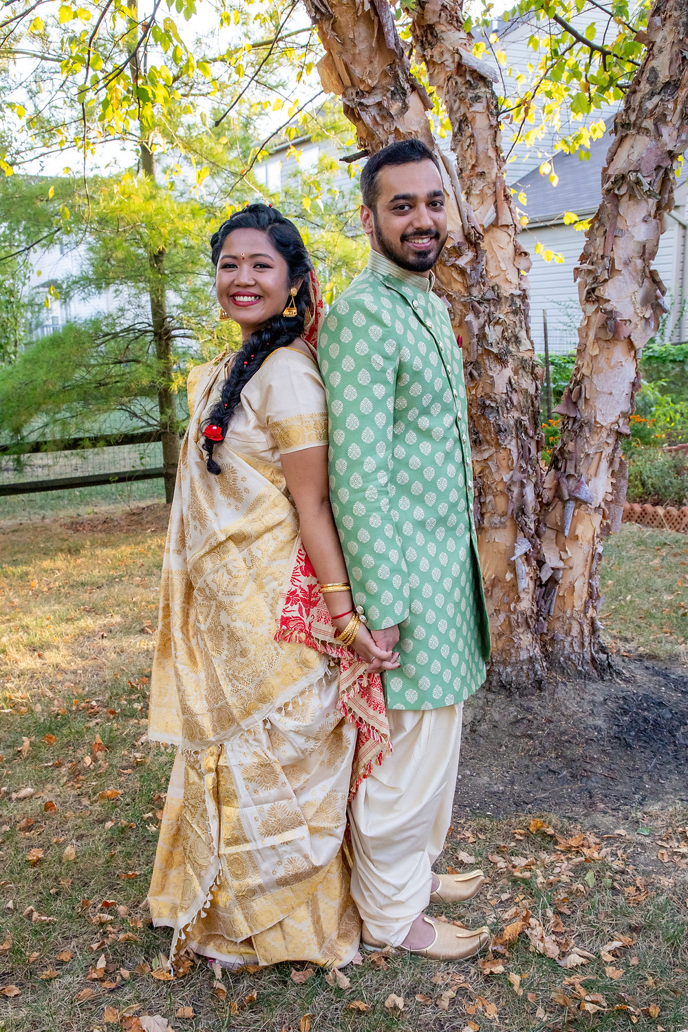 Indian wedding photographer captures image of indian husband and wife facing backwards of each other smiling for a picture holding hands.
