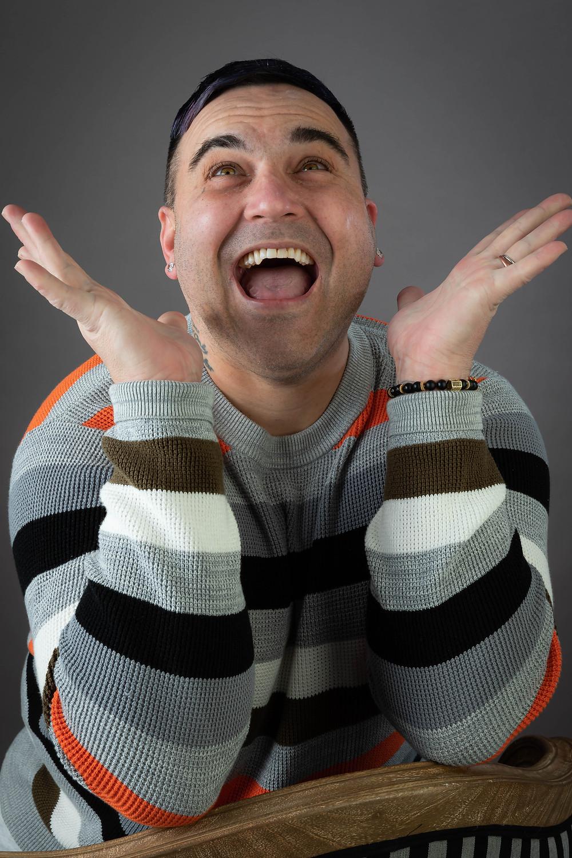 Cincinnati portrait photographer captures image of man excitedly smiling looking upwards with both hands up.