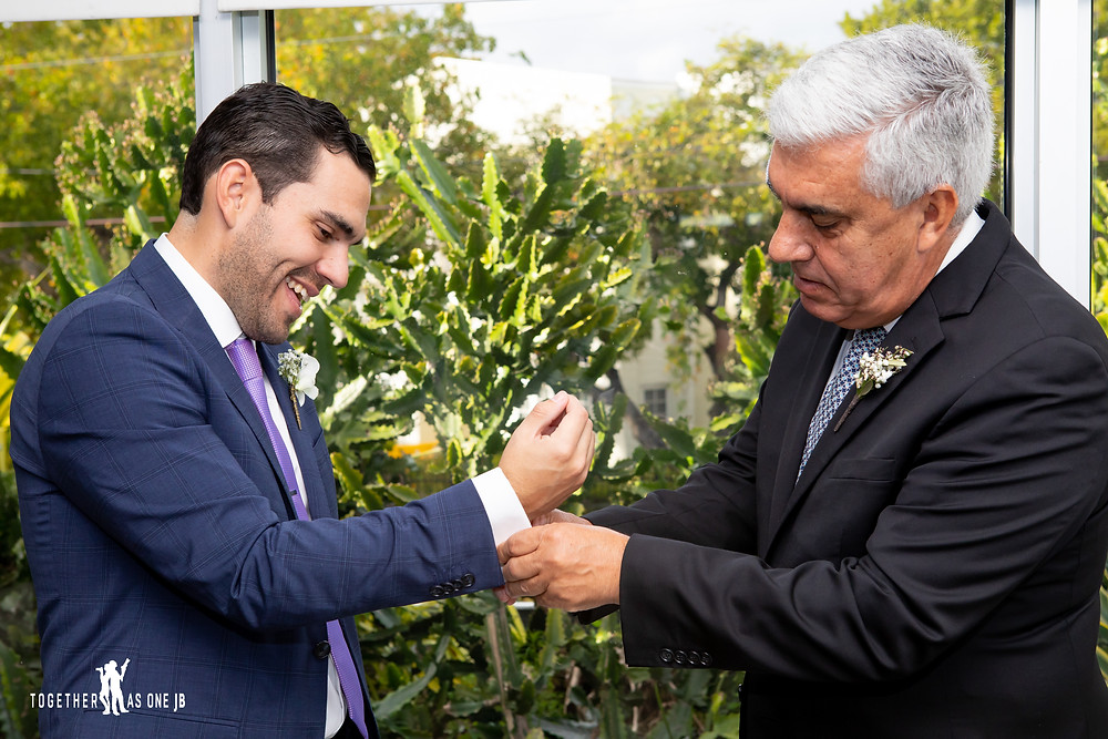 Groom's father helping groom with cufflinks in the M building in Wynwood
